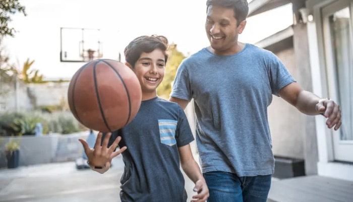 Spring HVAC maintenance as father and son play basketball