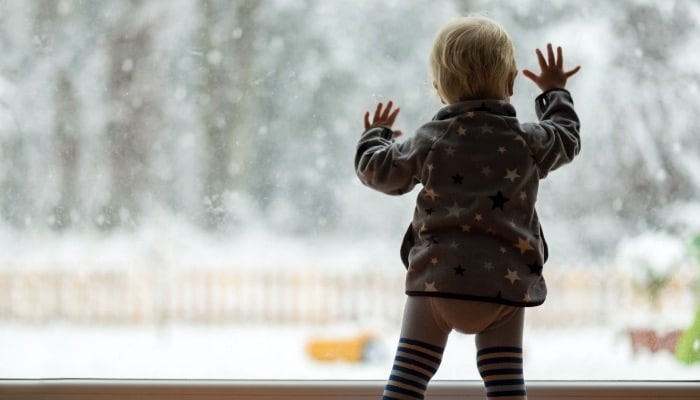 Toddler In Window Snowing Outside